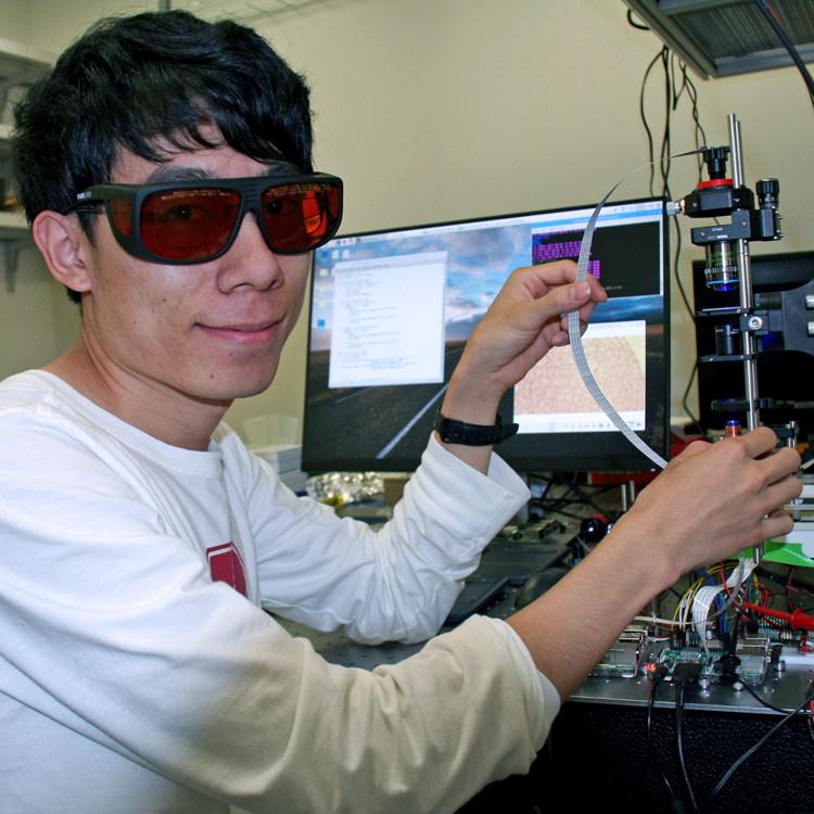 Photo of graduate student Hongquan Li in the lab, operating equipment while wearing red-tinted safety glasses.