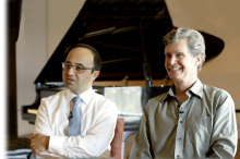 Drs. Josef Parvizi and Chris Chafe sitting next to each other in front of a piano.