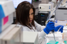 Photo of a female researcher in a lab coat and gloves pipetting into tubes in a laboratory area.