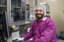 Photo of young male graduate student working in a clean room, gowned and wearing a cap while working on a computer.