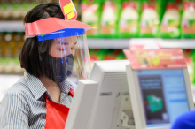 Photo of a female grocery store cashier wearing a mask and a face shield, checking out a shopper wearing a mask.