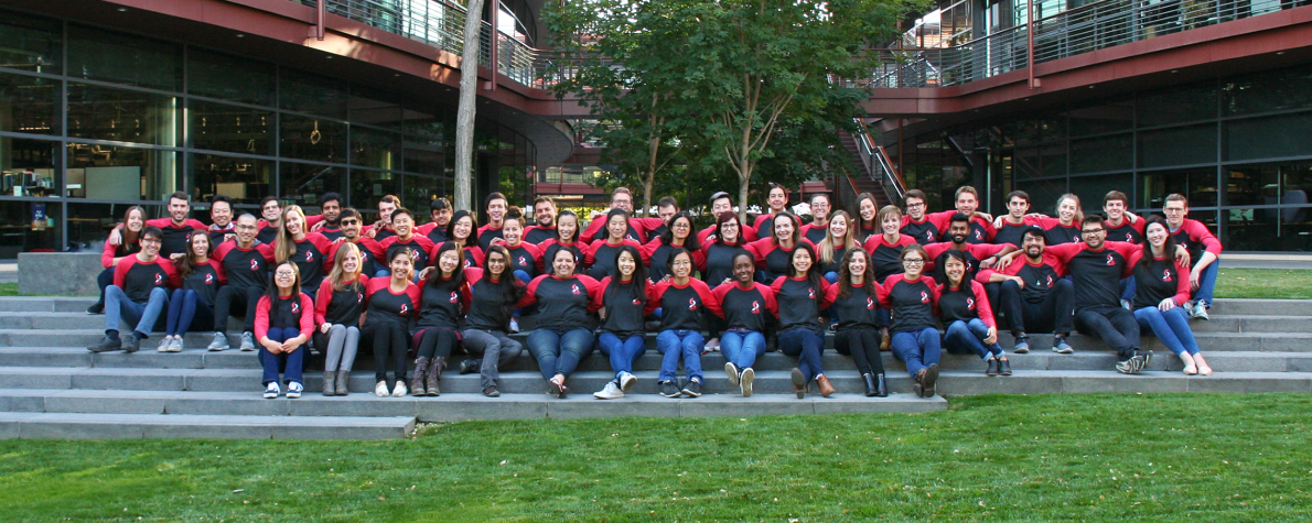 Group photo showing dozens of Stanford Bio-X graduate students seated on steps at the Clark Center, wearing matching shirts and with their arms around each other.